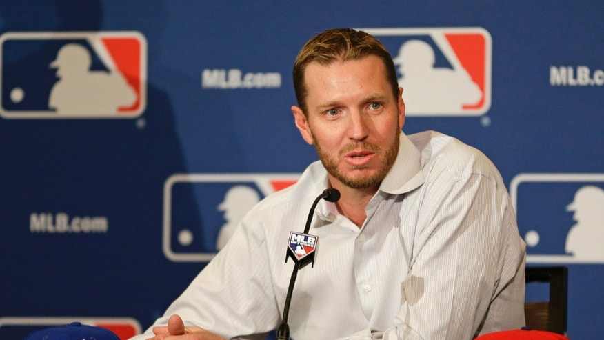 Two-time Cy Young Award winner Roy Halladay answers questions after announcing his retirement after 16 seasons in the major leagues with Toronto and Philadelphia at the MLB winter meetings in Lake Buena Vista, Fla., Monday, Dec. 9, 2013.(AP Photo/John Raoux)