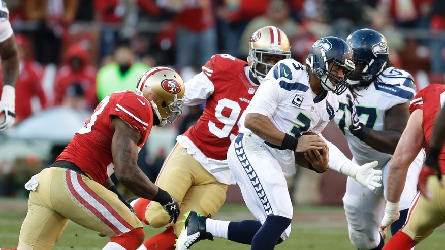 Seattle Seahawks quarterback Russell Wilson (3) keeps the ball as San Francisco 49ers inside linebacker NaVorro Bowman, and outside linebacker Aldon Smith, second from left, close in during the second half of an NFL football game, Sunday, Dec. 8, 2013, in San Francisco. (AP Photo/Ben Margot)