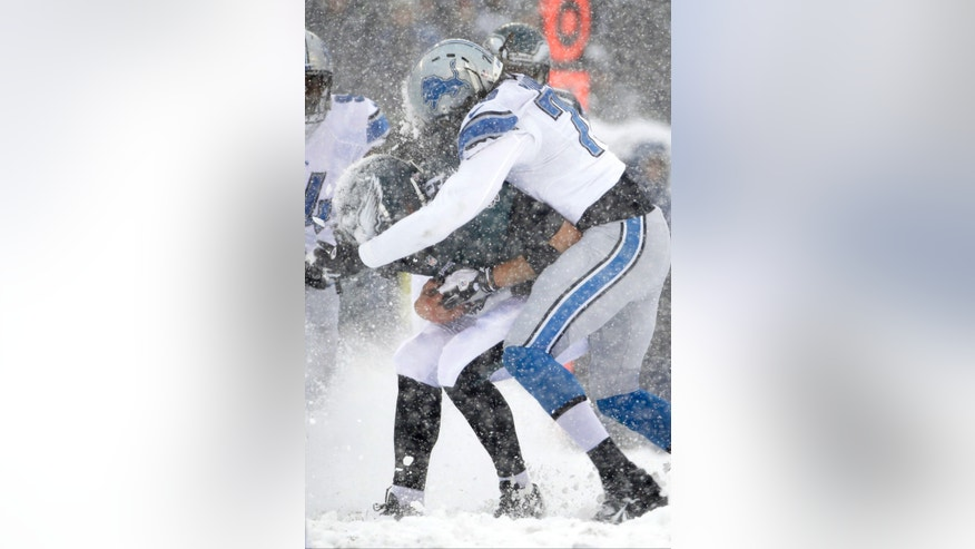 Philadelphia Eagles' Nick Foles, left, is tackled by Detroit Lions' Willie Young during the first half of an NFL football game, Sunday, Dec. 8, 2013, in Philadelphia. (AP Photo/Matt Rourke)