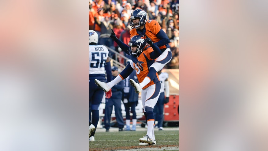 Denver Broncos kicker Matt Prater, bottom, celebrates 64-yard field goal with Britton Colquitt during the first half of an NFL football game against the Tennessee Titans on during the first half of an NFL football game on Sunday, Dec. 8, 2013, in Denver. (AP Photo/Jack Dempsey)