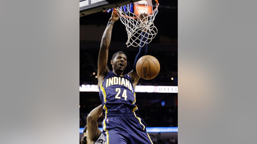 Indiana Pacers' Paul George (24) scores over San Antonio Spurs' Boris Diaw, of France, during the first half on an NBA basketball game, Saturday, Dec. 7, 2013, in San Antonio. (AP Photo/Eric Gay)