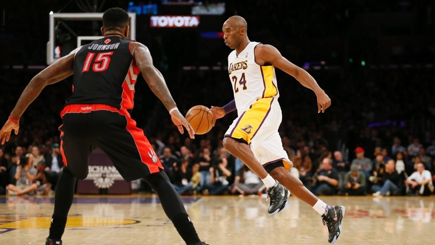 Los Angeles Lakers' Kobe Bryant dribbles the ball as Toronto Raptors' Amir Johnson, left, defends during the first half of an NBA basketball game in Los Angeles, Sunday, Dec. 8, 2013. (AP Photo/Danny Moloshok)