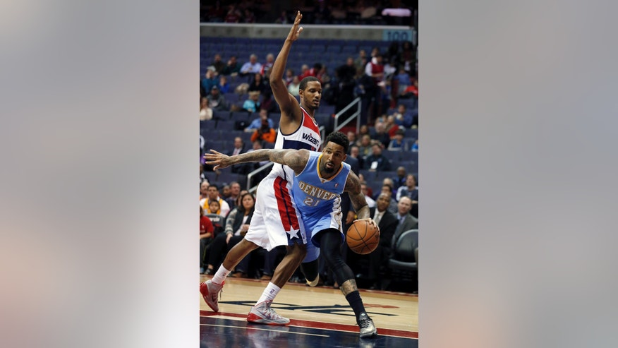 Denver Nuggets forward Wilson Chandler (21) drives around Washington Wizards forward Trevor Ariza, left, in the first half of an NBA basketball game on Monday, Dec. 9, 2013, in Washington. (AP Photo/Alex Brandon)