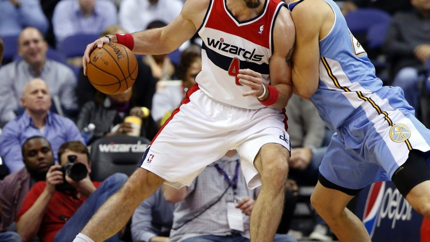 Washington Wizards center Marcin Gortat (4), from Poland, drives against Denver Nuggets center Timofey Mozgov, right, from Russia, in the first half of an NBA basketball game on Monday, Dec. 9, 2013, in Washington. (AP Photo/Alex Brandon)