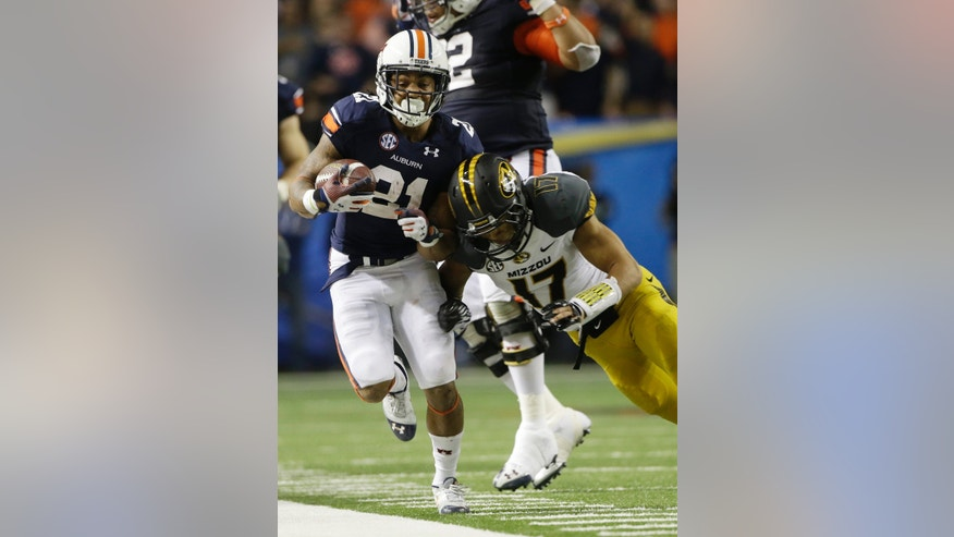 Auburn running back Tre Mason (21) runs against Missouri safety Matt White (17) during the second half of the Southeastern Conference NCAA football championship game, Saturday, Dec. 7, 2013, in Atlanta. (AP Photo/John Bazemore)
