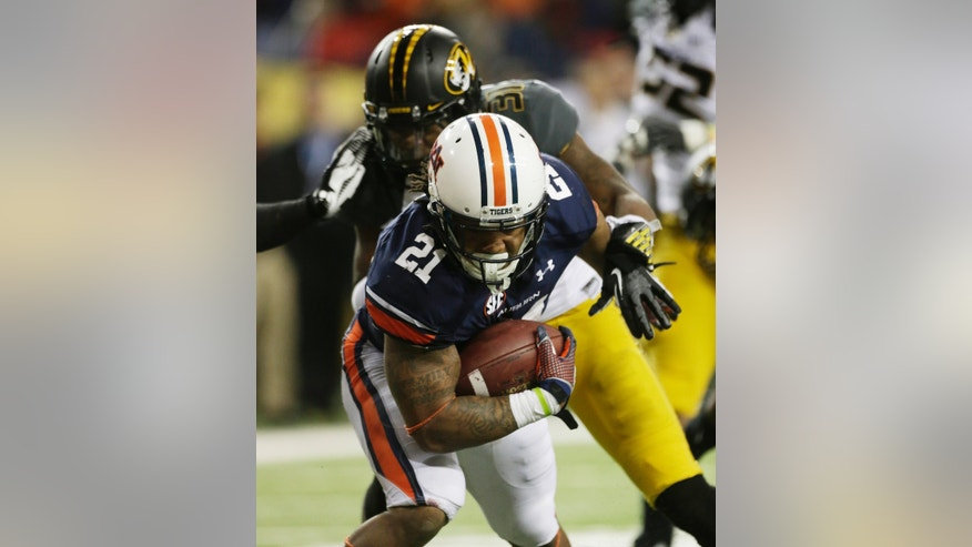 Auburn running back Tre Mason (21) runs into the end zone against Missouri defensive back E.J. Gaines (31)  during the second half of the Southeastern Conference NCAA football championship game, Saturday, Dec. 7, 2013, in Atlanta. (AP Photo/Dave Martin)