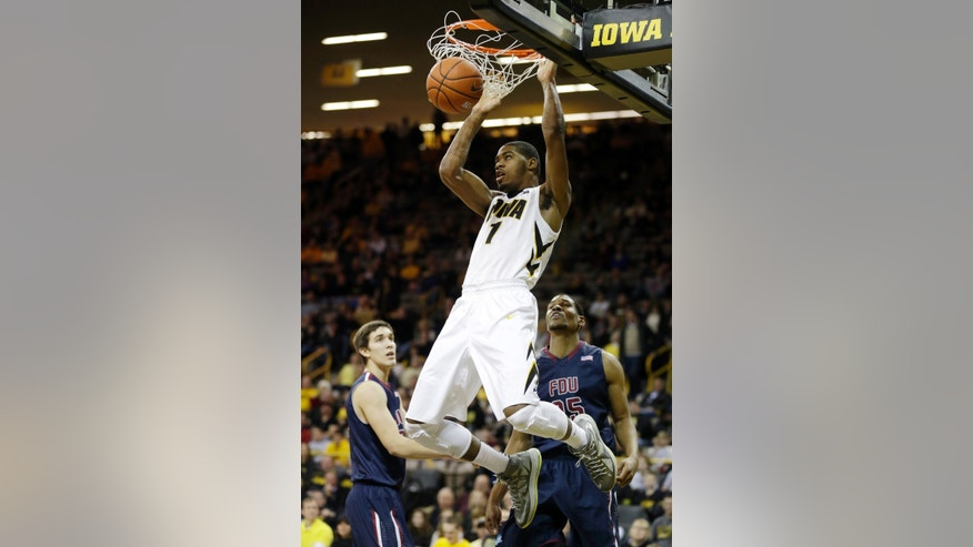 Iowa forward Melsahn Basabe (1) dunks the ball over Fairleigh Dickinson's Matt MacDonald, left, and Scooter Gillette, right, during the first half of an NCAA college basketball game, Monday, Dec. 9, 2013, in Iowa City, Iowa. (AP Photo/Charlie Neibergall)