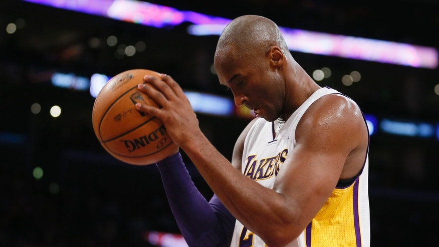 Los Angeles Lakers' Kobe Bryant reacts to a whistle shortly after turning over the ball against the Toronto Raptors in the second half of an NBA basketball game in Los Angeles, Sunday, Dec. 8, 2013.  It was Bryant's first game back after a torn left Achilles tendon injury on April 12, and the Raptors won 106-94. (AP Photo/Danny Moloshok)
