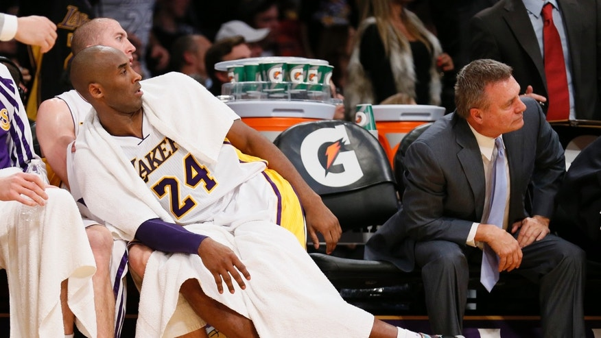 Los Angeles Lakers' Kobe Bryant leans over onto teammate Steve Blake's lap next to assistant coach Dan D'Antoni, right, as they watch Shawne Williams make a three-pointer against the Toronto Raptors in the second half of an NBA basketball game in Los Angeles, Sunday, Dec. 8, 2013.  It was Bryant's first game back after a torn left Achilles tendon injury and the Raptors won 106-94. (AP Photo/Danny Moloshok)