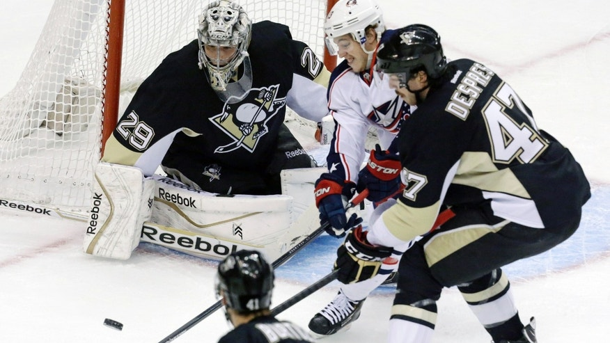Columbus Blue Jackets center Boone Jenner, center, can't get a shot off between Pittsburgh Penguins goalie Marc-Andre Fleury (29) and Pittsburgh Penguins' Simon Despres (47) in the first period of an NHL hockey game in Pittsburgh, Monday, Dec. 9, 2013. (AP Photo/Gene J. Puskar)