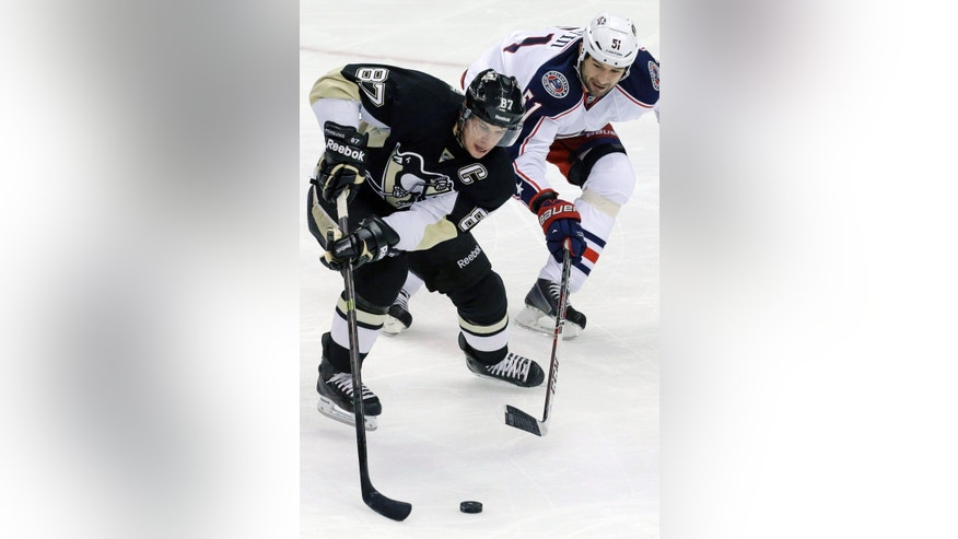 Pittsburgh Penguins' Sidney Crosby (87) skates around Columbus Blue Jackets'  Fedor Tyutin (51) in the first period of an NHL hockey game in Pittsburgh, Monday, Dec. 9, 2013. (AP Photo/Gene J. Puskar)