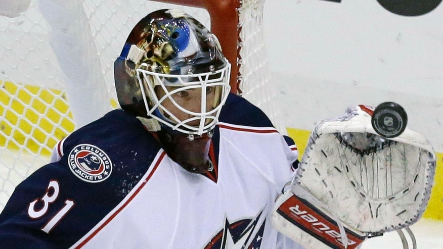 Columbus Blue Jackets goalie Curtis McElhinney deflects the puck with his glove hand on a shot in the first period of an NHL hockey game against the Pittsburgh Penguins in Pittsburgh, Monday, Dec. 9, 2013. (AP Photo/Gene J. Puskar)