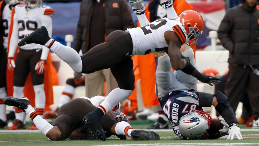 Cleveland Browns safety T.J. Ward, left, and linebacker D'Qwell Jackson, top, tackle New England Patriots tight end Rob Gronkowski (87) after a catch in the third quarter of an NFL football game on Sunday, Dec. 8, 2013, in Foxborough, Mass. (AP Photo/Elise Amendola)