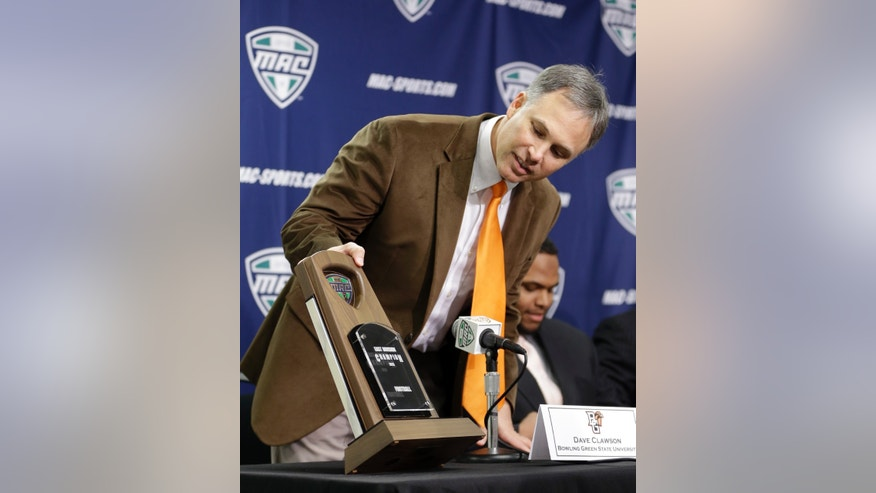 Bowling Green head coach Dave Clawson looks over the Mid-American Conference East Championship trophy before a press conference at Ford Field in Detroit, Thursday, Dec. 5, 2013. Bowling Green will play Northern Illinois in the MAC Championship football game on Friday night. (AP Photo/Carlos Osorio)