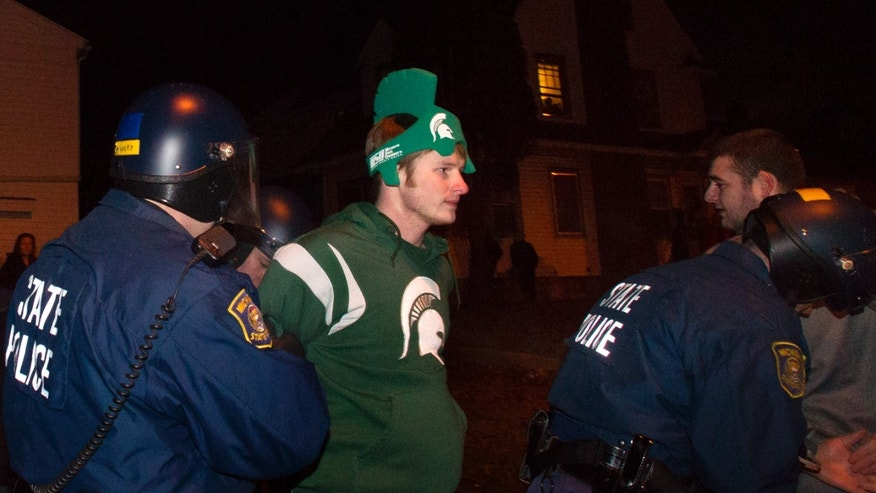 Members of the Michigan State Police Department arrest unruly celebrants, early Sunday, Dec. 8, 2013,  in East Lansing's Cedar Village.  Thousands of Michigan State students celebrated the football team's Big Ten title with large, rowdy bonfires. East Lansing police arrested multiple people Saturday night near River and Cedar streets, which is a traditional spot for MSU students to party after major sports victories. No. 10 MSU defeated No. 2 Ohio State 34-24 late Saturday, earning its first Rose Bowl appearance in a quarter-century. (AP Photo/The State Journal, Matthew Dae Smith)  NO SALES
