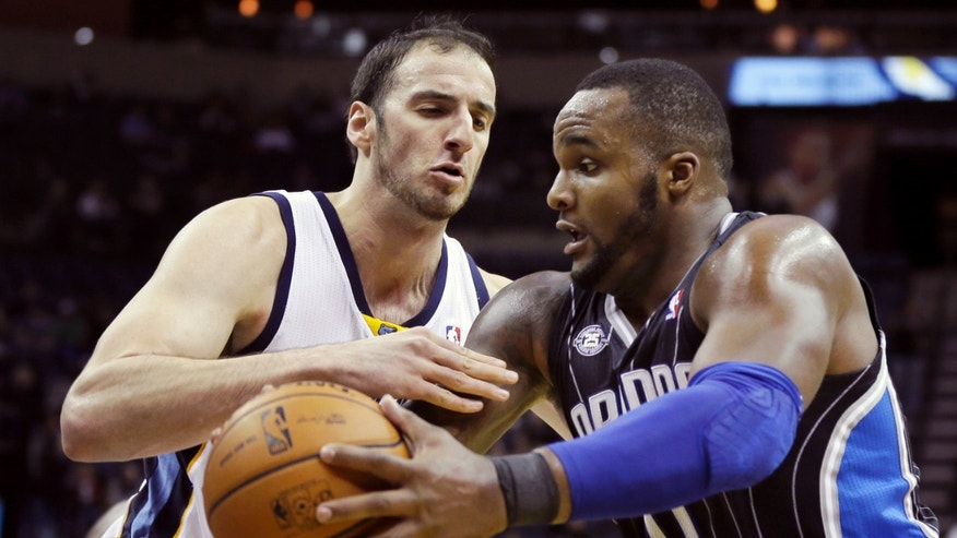 Memphis Grizzlies' Kosta Koufos, left, defends against Orlando Magic's Glen Davis, right, in the first half of an NBA basketball game in Memphis, Tenn., Monday, Dec. 9, 2013. (AP Photo/Danny Johnston)