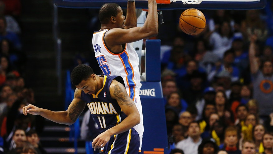 Oklahoma City Thunder forward Kevin Durant (35) dunks behind Indiana Pacers guard Orlando Johnson (11) in the fourth quarter of an NBA basketball game in Oklahoma City, Sunday, Dec. 8, 2013. Oklahoma City won 118-94. (AP Photo/Sue Ogrocki)