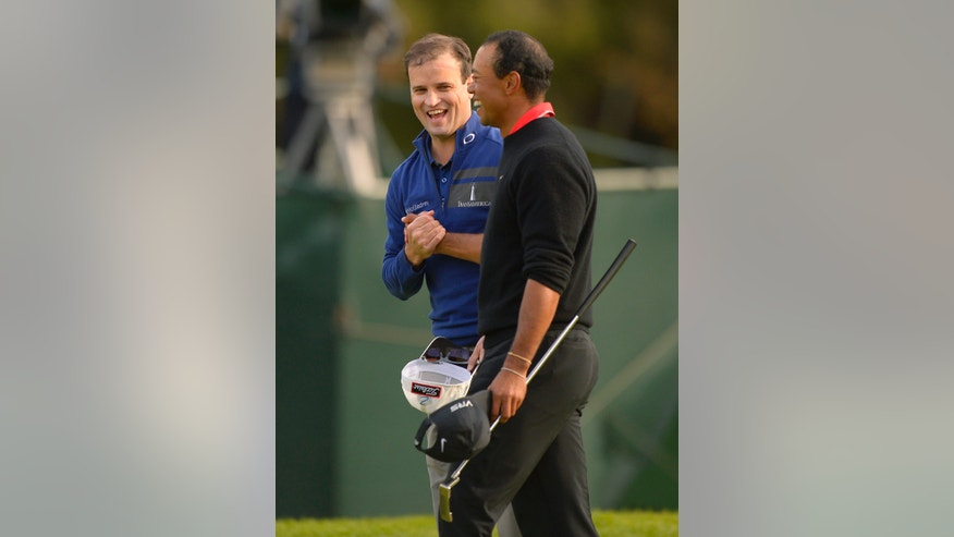 Zach Johnson, left, and Tiger Woods shake hands after finishing their round tie and forcing a playoff during the final round of the Northwestern Mutual World Challenge golf tournament at Sherwood Country Club, Sunday, Dec. 8, 2013, in Thousand Oaks, Calif. (AP Photo/Mark J. Terrill)