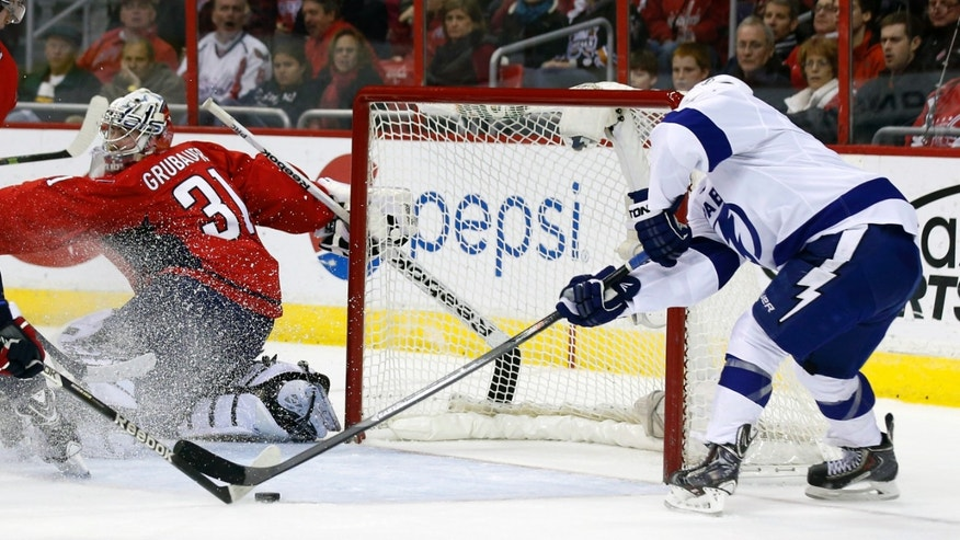 Tampa Bay Lightning center Tyler Johnson, right, reaches for the puck to score a goal past Washington Capitals goalie Philipp Grubauer (31), of Germany, in the second period of an NHL hockey game, Tuesday, Dec. 10, 2013, in Washington. (AP Photo/Alex Brandon)
