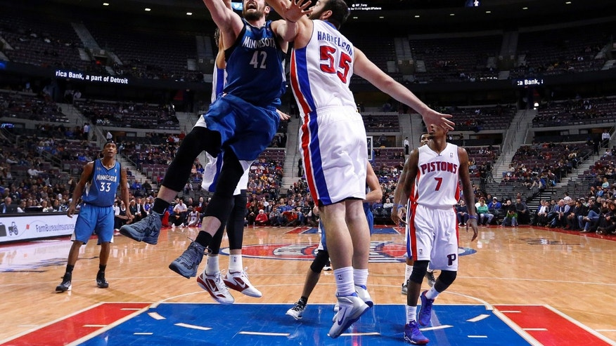 Minnesota Timberwolves power forward Kevin Love (42) drives on Detroit Pistons power forward Josh Harrellson (55) in the first half of an NBA basketball game in Auburn Hills, Mich., Tuesday, Dec. 10, 2013. (AP Photo/Paul Sancya)