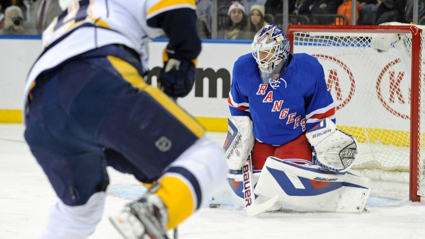 New York Rangers goaltender Henrik Lundqvist, right, of Sweden, makes a save during the first period of an NHL hockey game against the Nashville Predators Tuesday, Dec. 10, 2013, in New York. (AP Photo/Bill Kostroun)