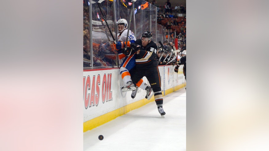 Anaheim Ducks defenseman Mark Fistric, right, puts New York Islanders right wing Cal Clutterbuck into the boards during the first period of an NHL hockey game, Monday, Dec. 9, 2013, in Anaheim, Calif. (AP Photo/Mark J. Terrill)