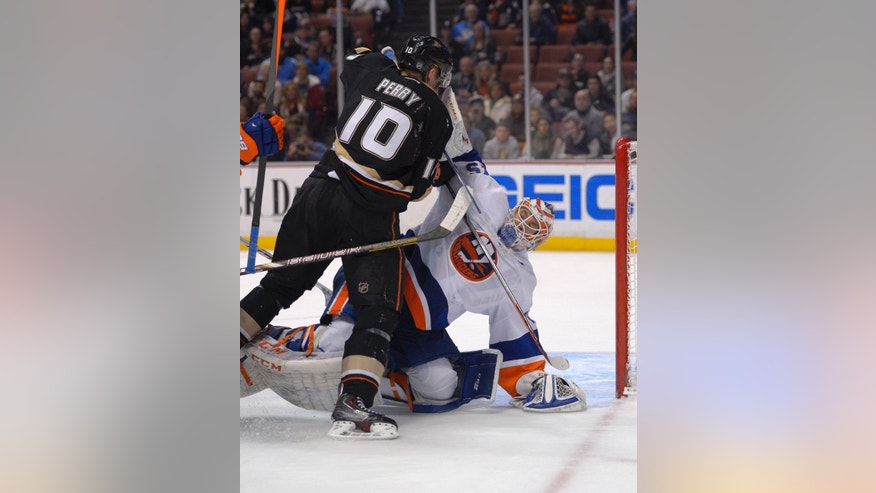 New York Islanders goalie Anders Nilsson, of Sweden, puts his blocker in the face of Anaheim Ducks right wing Corey Perry during the second period of an NHL hockey game, Monday, Dec. 9, 2013, in Anaheim, Calif. (AP Photo/Mark J. Terrill)