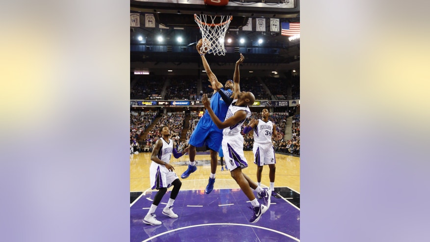 Dallas Mavericks guard Vince Carter, second from left, drives to the basket against Sacramento Kings forward Travis Outlaw, second from right, as Kings' Ben McLemore, left, and Jason Thompson, right, look on during the first half of an NBA basketball game in Sacramento, Calif., Monday, Dec. 9, 2013. (AP Photo/Rich Pedroncelli)