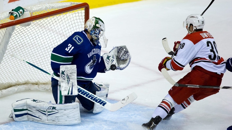 Vancouver Canucks' goalie Eddie Lack, left, of Sweden, stops Carolina Hurricanes' Patrick Dwyer during the second period of an NHL hockey game in Vancouver, British Columbia on Monday, Dec. 9, 2013. (AP Photo/The Canadian Press, Darryl Dyck)
