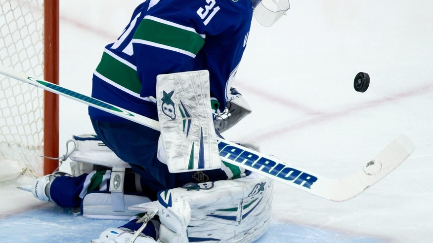 Vancouver Canucks' goalie Eddie Lack, of Sweden, makes a save against the Carolina Hurricanes during the second period of an NHL hockey game in Vancouver, British Columbia on Monday, Dec. 9, 2013. (AP Photo/The Canadian Press, Darryl Dyck)