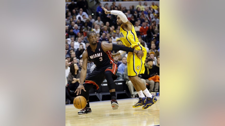 Miami Heat guard Dwyane Wade, left, drives on Indiana Pacers guard C.J. Watson in the first half of an NBA basketball game in Indianapolis, Tuesday, Dec. 10, 2013. (AP Photo/Michael Conroy)