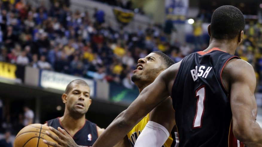 Indiana Pacers forward Paul George, center, is fouled by Miami Heat center Chris Bosh (1) as Miami Heat forward Shane Battier is near in the second half of an NBA basketball game in Indianapolis, Tuesday, Dec. 10, 2013. The Pacers won 90-84. (AP Photo/Michael Conroy)