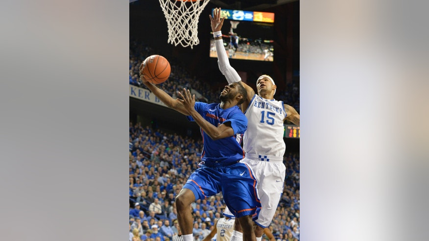 Boise State's Mikey Thompson, left, attempts a layup past the defense of Kentucky's Willie Cauley-Stein during the first half of an NCAA college basketball game Tuesday, Dec. 10, 2013, in Lexington, Ky. (AP Photo/Timothy D. Easley)