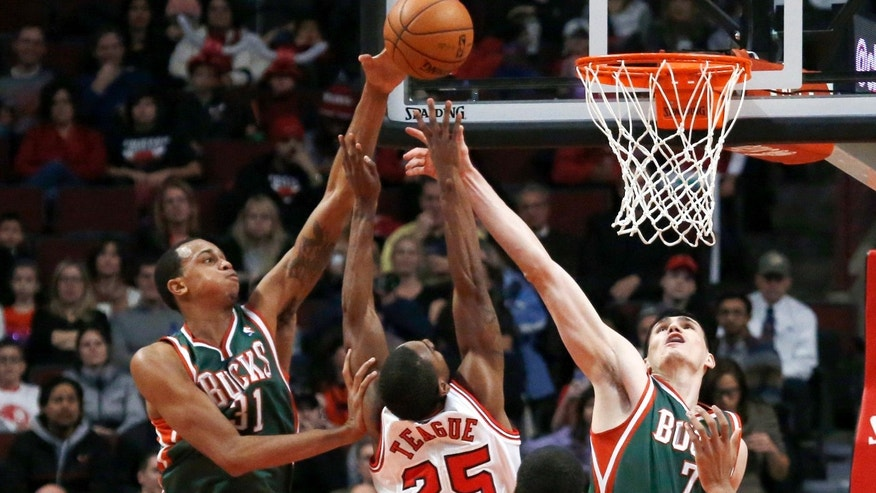 Milwaukee Bucks forward John Henson, left, blocks the shot of Chicago Bulls point guard Marquis Teague (25) as Ersan Ilyasova (7) also defends during the first half of an NBA basketball game Tuesday, Dec. 10, 2013, in Chicago. (AP Photo/Charles Rex Arbogast)