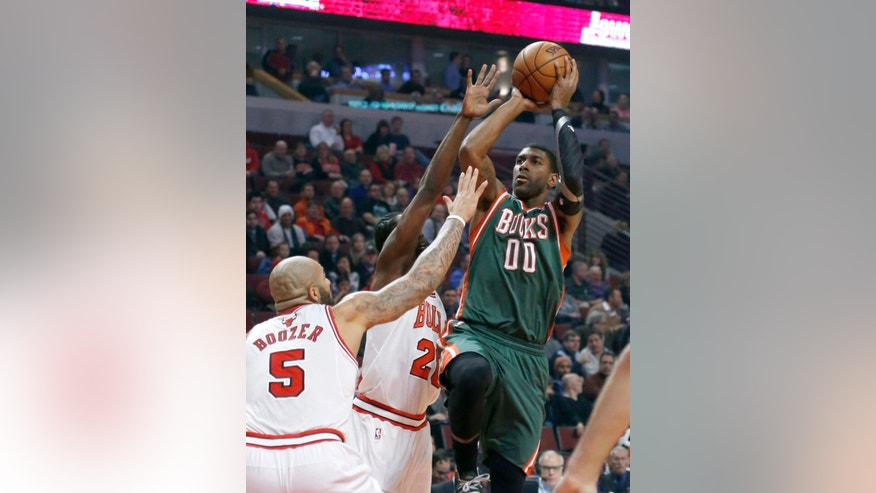 Milwaukee Bucks shooting guard O.J. Mayo (00) shoots over Chicago Bulls forward Carlos Boozer (5) and Tony Snell during the first half of an NBA basketball game Tuesday, Dec. 10, 2013, in Chicago. (AP Photo/Charles Rex Arbogast)