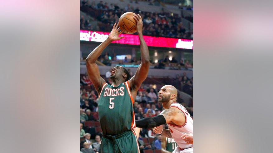 Milwaukee Bucks forward Ekpe Udoh (5) is fouled from behind by Chicago Bulls forward Carlos Boozer during the first half of an NBA basketball game Tuesday, Dec. 10, 2013, in Chicago. (AP Photo/Charles Rex Arbogast)