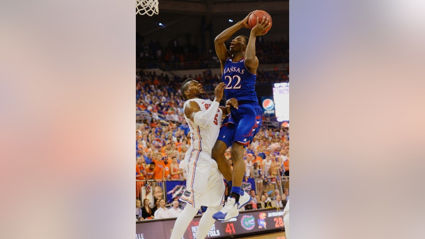 Kansas guard Andrew Wiggins (22) goes for two points with Florida forward Will Yeguete (15) trying to stop the shot during the second half of an NCAA college basketball game Tuesday, Dec. 10, 2013 in Gainesville, Fla. Florida defeated the University of Kansas 67-61.  (AP Photo/Phil Sandlin)