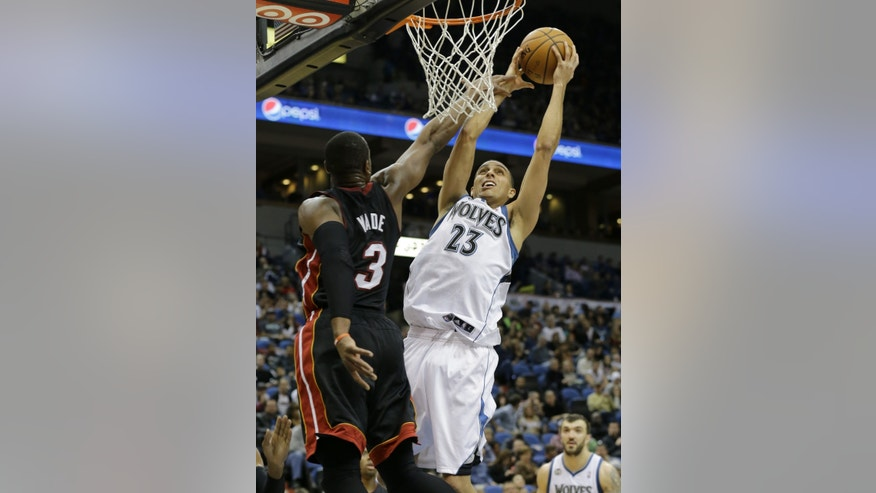 Minnesota Timberwolves guard Kevin Martin (23) is fouled by Miami Heat shooting guard Dwyane Wade (3) while shooting during the fourth quarter of an NBA basketball game in Minneapolis, Saturday, Dec. 7, 2013. Martin had a team high 19 points as the Heat defeated the Timberwolves 103-82. (AP Photo/Ann Heisenfelt)
