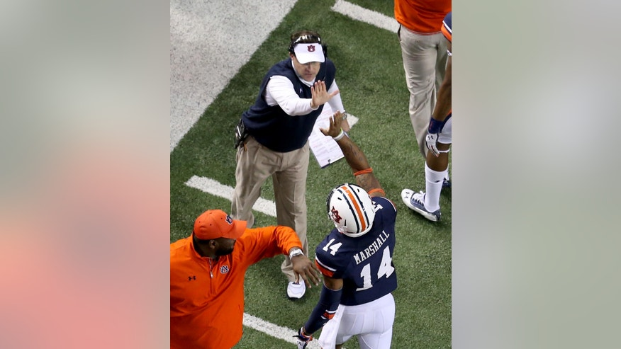 Auburn coach Gus Malzahn, top, high fives quarterback Nick Marshall (14) after an Auburn touchdown in the third quarter of Auburn's 59-42 win over Missouri in the SEC Championship Saturday night in Atlanta, Ga., Dec. 7, 2013. (AP Photo/Atlanta Journal-Constitution, Jason Getz)