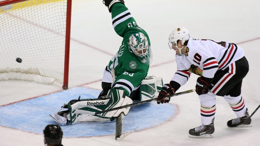 Dallas Stars goalie Dan Ellis (30) gives up a goal to Chicago Blackhawks left wing Patrick Sharp (10) in the second period of an NHL hockey game Tuesday, Dec. 10, 2013, in Dallas, Texas. (AP Photo/Sharon Ellman)