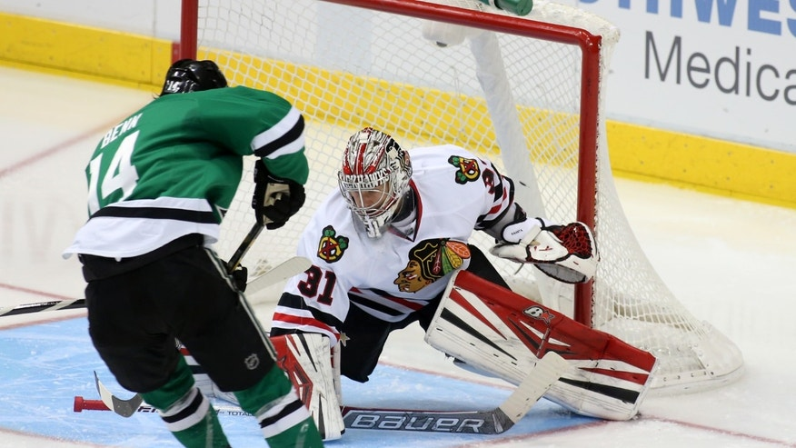 Dallas Stars center Jamie Benn (14) takes a shot on Chicago Blackhawks goalie Antti Raanta (31), of FInland, in the second period of an NHL hockey game Tuesday, Dec. 10, 2013, in Dallas. (AP Photo/Sharon Ellman)