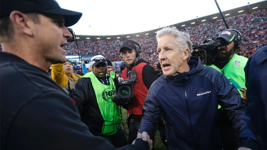 San Francisco 49ers head coach Jim Harbaugh, left, shakes hands with Seattle Seahawks head coach Pete Carroll, right, at the end of an NFL football game, Sunday, Dec. 8, 2013, in San Francisco. The 49ers defeated the Seahawks 19-17. (AP Photo/Marcio Jose Sanchez)