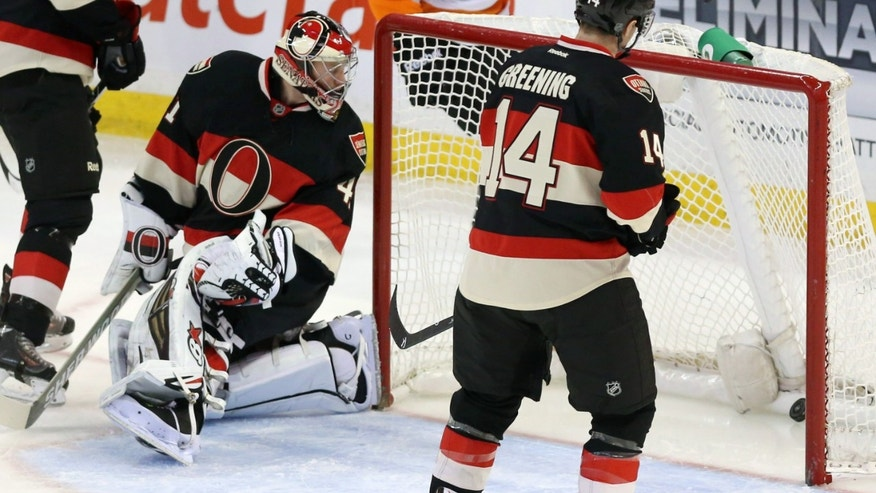 Ottawa Senators goaltender Craig Anderson (41) looks at the puck as teammates Chris Phillips (4) Colin Greening (14) look on after Philadelphia Flyer's Michael Raffi (12) scored during first period of an NHL hockey game on Monday, Dec. 9, 2013. in Ottawa, Ontario. (AP Photo/The Canadian Press, Fred Chartrand)