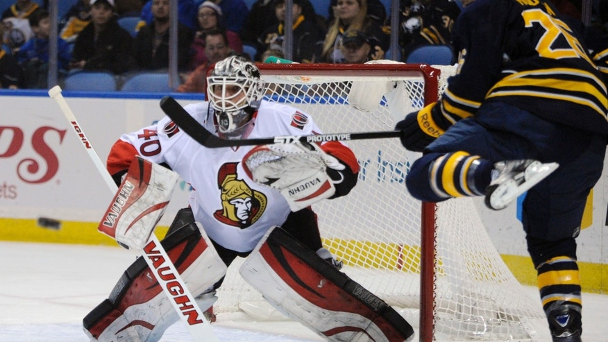 Ottawa Senators goaltender Robin Lehner (40) keeps an eye on an incoming puck as Buffalo Sabres left winger Matt Moulson (26) gets his stick up to deflect the shot  during the first period of an NHL hockey game in Buffalo, N.Y., Tuesday, Dec. 10, 2013. (AP Photo/Gary Wiepert)
