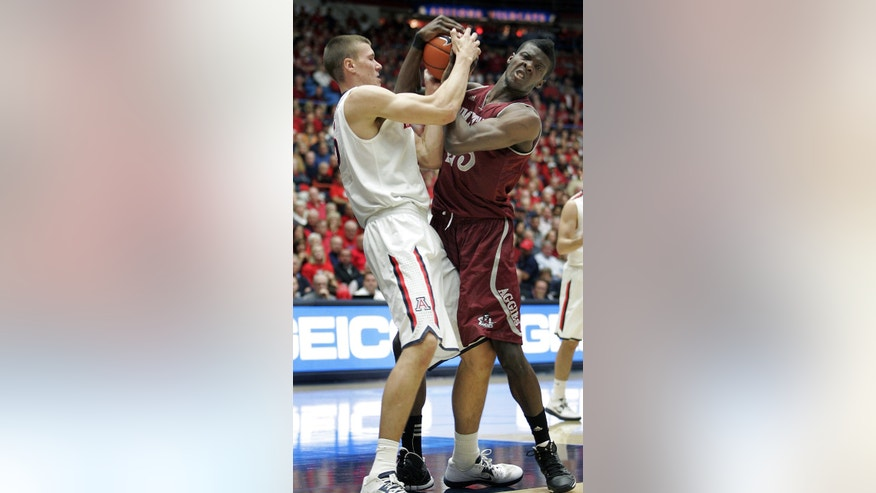 Arizona's Kaleb Tarczewski, left, and New Mexico States' Renaldo Dixon, right, battle for control of the ball in the first half of an NCAA college basketball game on Wednesday, Dec. 11, 2013 in Tucson, Ariz. (AP Photo/John MIller)