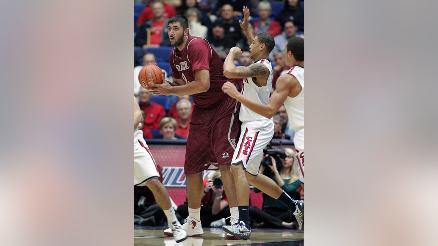 New Mexico States' Sim Bhullar, left, looks to pass the ball against the defense of Arizona's Brandon Ashley, right, in the first half of an NCAA college basketball game on Wednesday, Dec. 11, 2013 in Tucson, Ariz. (AP Photo/John MIller)