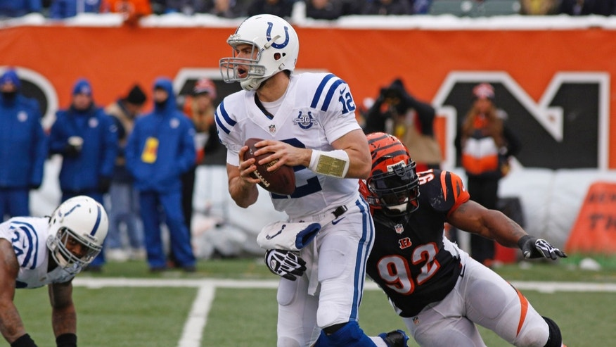 Indianapolis Colts quarterback Andrew Luck (12) is pursued by Cincinnati Bengals outside linebacker James Harrison (92) in the first half of an NFL football game, Sunday, Dec. 8, 2013, in Cincinnati. (AP Photo/David Kohl)