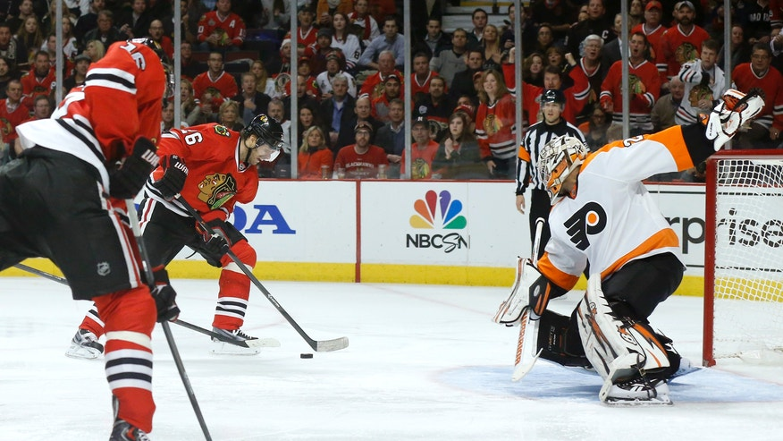 Chicago Blackhawks center Michal Handzus (26) scores past Philadelphia Flyers goalie Ray Emery, right, off a pass from Marcus Kruger, left, during the second period of an NHL hockey game on Wednesday, Dec. 11, 2013, in Chicago. (AP Photo/Charles Rex Arbogast)