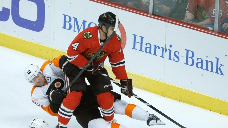 Philadelphia Flyers left wing Scott Hartnell (19) battles Chicago Blackhawks defenseman Niklas Hjalmarsson (4) for a loose puck during the first period of an NHL hockey game on Wednesday, Dec. 11, 2013, in Chicago. (AP Photo/Charles Rex Arbogast)