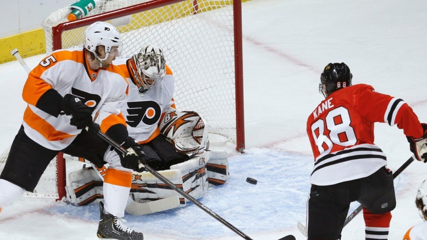 Philadelphia Flyers goalie Ray Emery, center, makes a save on a shot by Chicago Blackhawks right wing Patrick Kane (88) as Flyers' Braydon Coburn (5) also defends during the first period of an NHL hockey game on Wednesday, Dec. 11, 2013, in Chicago. (AP Photo/Charles Rex Arbogast)